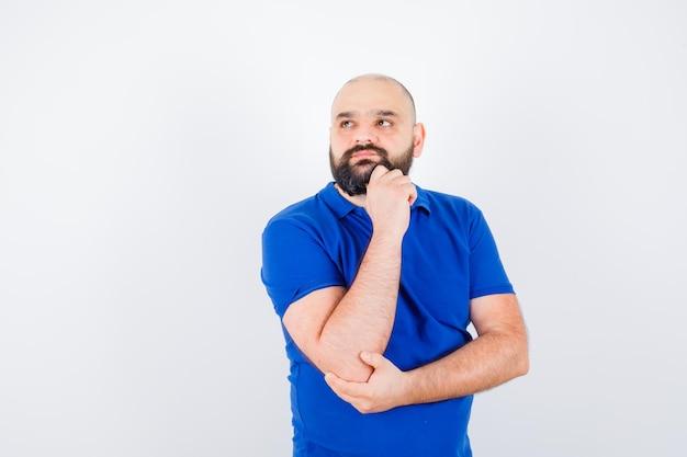 Jonge man in blauw shirt die wegkijkt en attent kijkt, vooraanzicht.