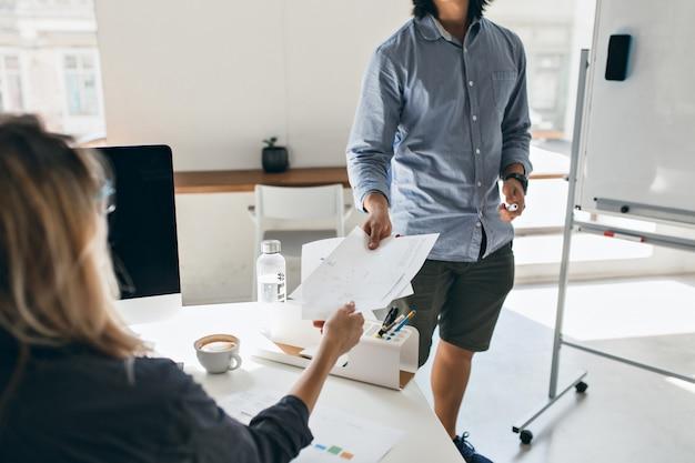Jonge man in blauw shirt en korte broek met documenten, wandelen door collega tafel. indoor portret van blonde vrouw koffie drinken in kantoor en flip-over kijken.