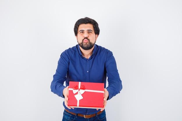 Jonge man in blauw shirt en spijkerbroek die een geschenkdoos met beide handen presenteert en kusjes stuurt en er optimistisch uitziet, vooraanzicht.