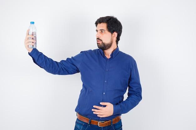 Jonge man in blauw shirt en spijkerbroek die een waterfles vasthoudt, ernaar kijkt en de hand op de buik houdt en er gefocust uitziet, vooraanzicht.