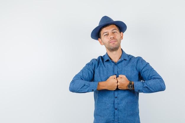 Jonge man in blauw shirt, hoed die vuisten vasthoudt en er zelfverzekerd uitziet, vooraanzicht.