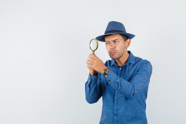 Jonge man in blauw shirt, hoed kijkend door vergrootglas, vooraanzicht.