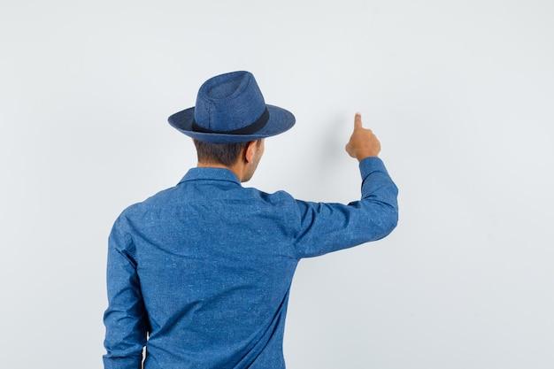 Jonge man in blauw shirt, hoed wijzend naar iets op de muur en gefocust, achteraanzicht.