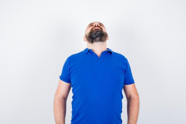 Jonge man in blauw shirt kijkt omhoog en kijkt gefocust, vooraanzicht.