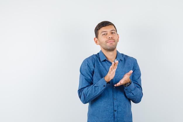 Jonge man in blauw shirt klappen na geweldige presentatie en opgetogen kijken, vooraanzicht.