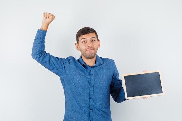Jonge man in blauw shirt met bord met winnaargebaar en gelukkig, vooraanzicht.