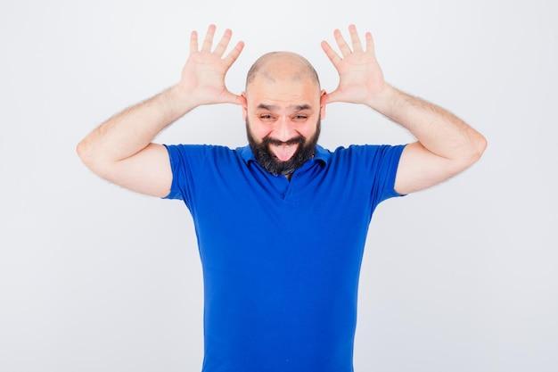 Jonge man in blauw shirt met hoornteken terwijl hij zijn tong uitsteekt en er grappig uitziet, vooraanzicht.