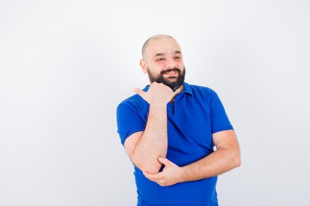 Jonge man in blauw shirt met telefoontje gebaar, vooraanzicht.