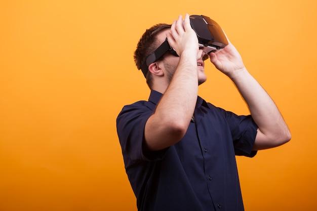 Jonge man in blauw shirt met vr-headset over gele achtergrond. nieuwe technologie