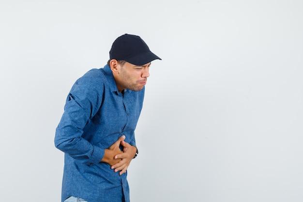 Jonge man in blauw shirt, pet die last heeft van buikpijn en er onwel uitziet, vooraanzicht.