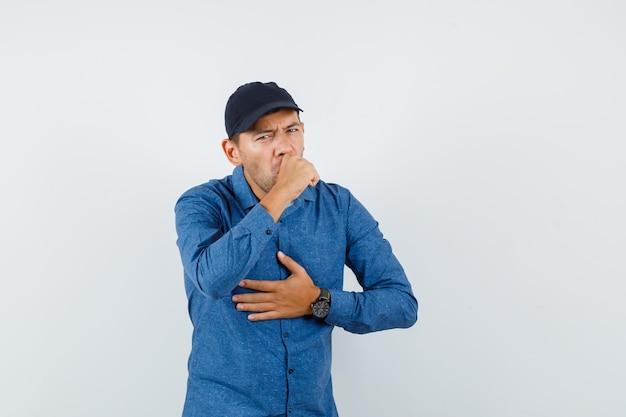 Jonge man in blauw shirt, pet met keelpijn en hoesten, vooraanzicht.