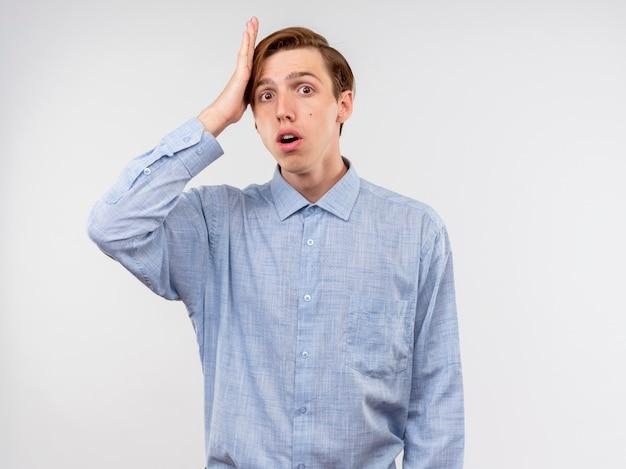 Jonge man in blauw shirt wordt verward en bezorgd met de hand op zijn hoofd voor een fout die zich over een witte muur bevindt