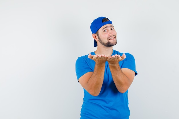 Jonge man in blauw t-shirt en pet die handpalmen opheft als iets presenteren en er vrolijk uitzien