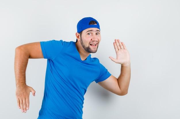 Jonge man in blauw t-shirt en pet gebaren als beweging maken en er grappig uitzien