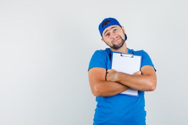Jonge man in blauw t-shirt en pet klembord stevig vasthouden en er vredig uitzien