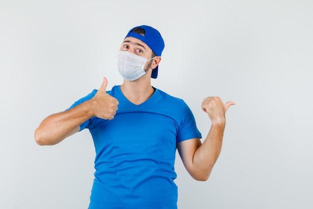 Jonge man in blauw t-shirt en pet, masker wijst weg met duim omhoog en kijkt zelfverzekerd