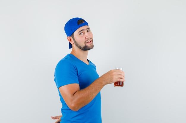 Jonge man in blauw t-shirt en pet met glas frisdrank en op zoek positief
