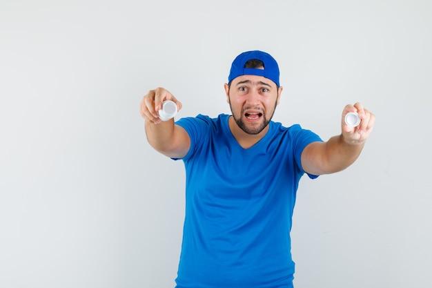 Jonge man in blauw t-shirt en pet met lege fles pillen en neergeslagen kijken.