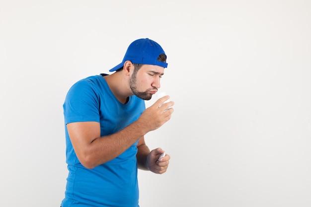 Jonge man in blauw t-shirt en pet ruiken open fles pillen