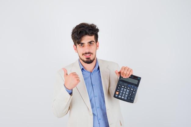 Jonge man in blauw t-shirt en wit jasje met rekenmachine en duim opdagen en er vriendelijk uitzien