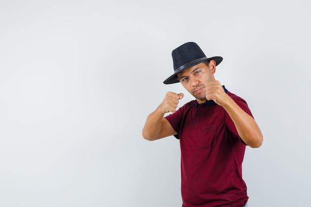 Jonge man in bokser pose in t-shirt, hoed en krachtig, vooraanzicht.