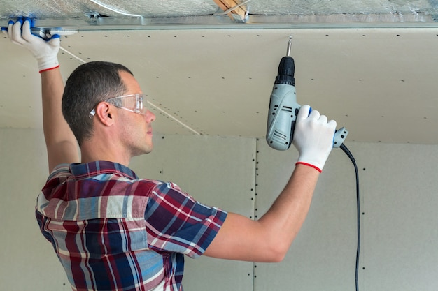Jonge man in bril die gipsplaten verlaagd plafond bevestigt aan metalen frame met behulp van elektrische schroevendraaier op plafond geïsoleerd met glanzende aluminiumfolie. renovatie, bouw, doe het zelf concept.