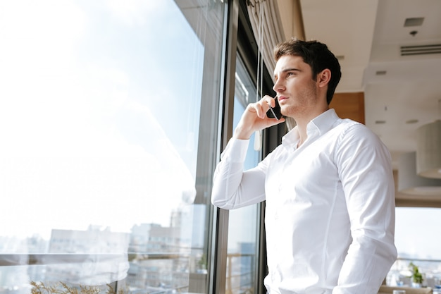 Jonge man in café praten via de mobiele telefoon.