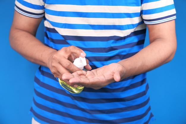 Jonge man in casual kleding met behulp van ontsmettingsmiddel gel tegen blauw
