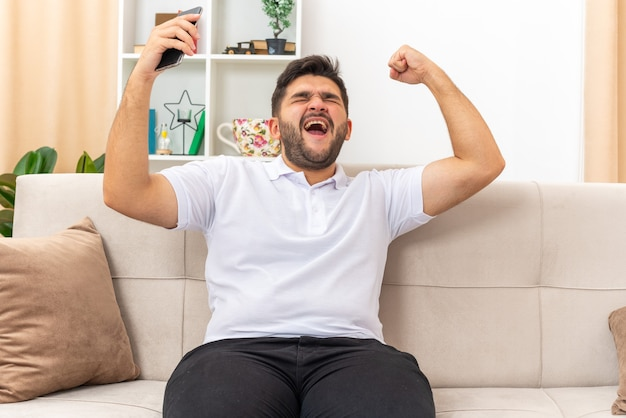 Jonge man in casual kleding met smartphone blij en opgewonden gebalde vuist verheugt zich over zijn succes zittend op een bank in lichte woonkamer