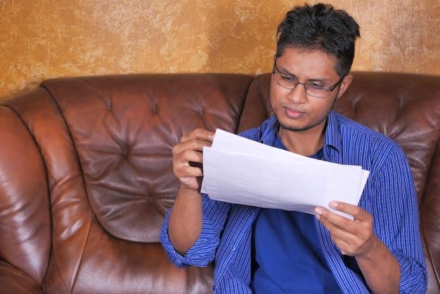 Jonge man in casual kleding zittend op de bank werken vanuit huis.