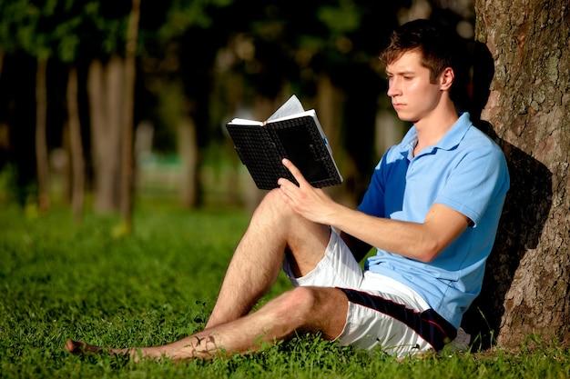 Jonge man in casual kleding zittend op het groene gras in de buurt van de boom en leesboek in park op heldere zomerdag. innerlijke vrijheid en gelukkig levensstijlconcept