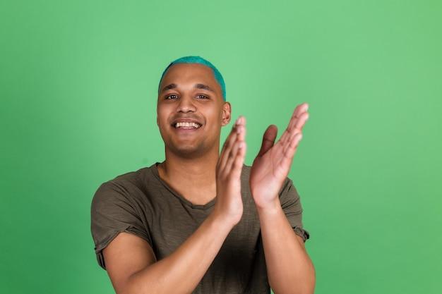 Jonge man in casual op groene muur blauw haar gelukkige positieve glimlach op zoek naar camera en juicht gefeliciteerd!