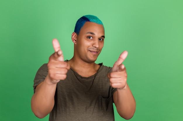Jonge man in casual op groene muur, blije glimlach wijst naar jou