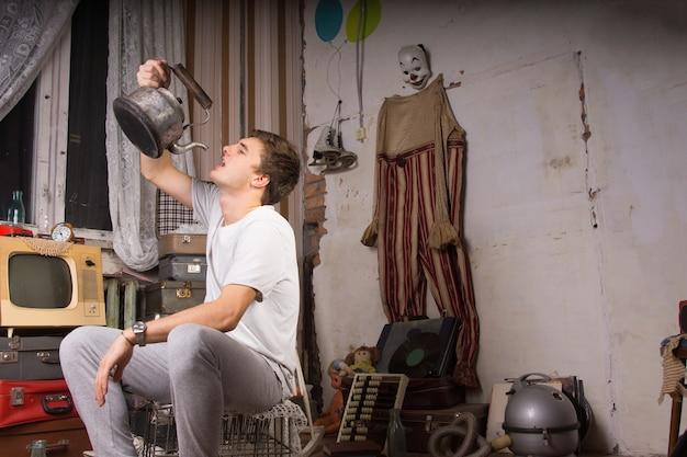 Jonge man in casual outfit die iets uit een oude waterkoker drinkt terwijl hij op de kooi zit.