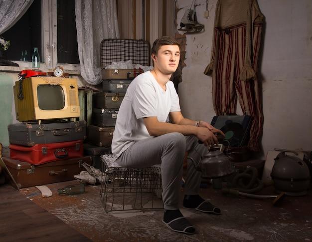 Jonge man in casual outfit zit in de rommelkamer en kijkt naar de camera.