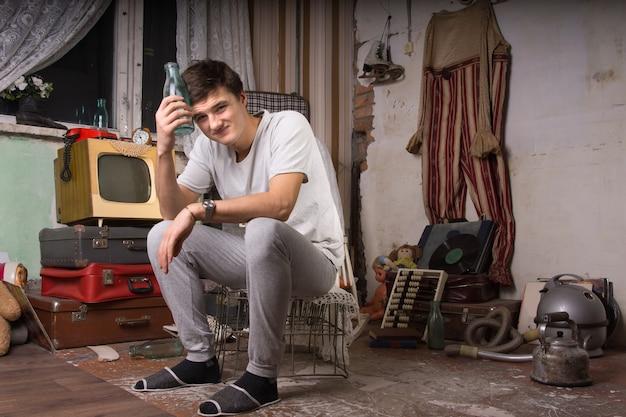 Jonge man in casual outfit zittend in rommelkamer met glazen fles terwijl hij naar de camera kijkt.
