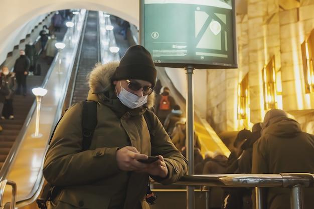 Jonge man in casual winterkleren met bril en medisch masker bij metro roltrap. aantrekkelijke tiener met telefoon in de metro van de grote stad, kijkend naar mobiele telefoon en emoties van een onverwachte e-mail
