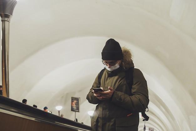 Jonge man in casual winterkleren met bril en medisch masker bij metro roltrap