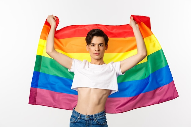 Jonge man in crop top, met glitters op het gezicht, trots vlag opheffen met zelfverzekerde emotie. vreemde persoon lachend met een lgbt-vlag.