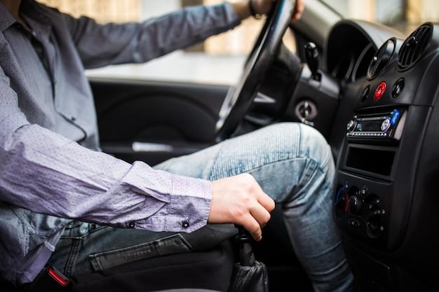 Jonge man in de auto schakelt versnelling