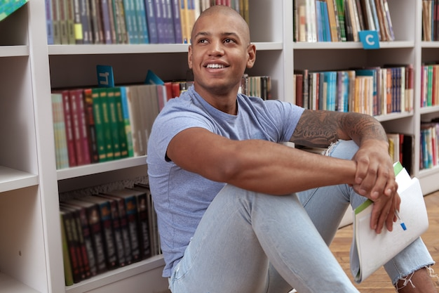 Jonge man in de bibliotheek of boekhandel