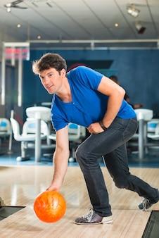 Jonge man in de bowlingbaan met plezier, de sportieve man die een bowlingbal speelt voor de kegelbaan