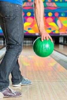 Jonge man in de bowlingbaan met plezier, de sportieve man met een bowlingbal voor de tien-pins baan