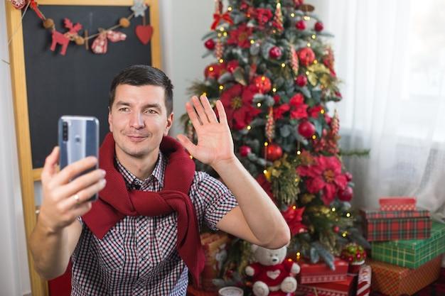 Jonge man in de buurt van de kerstboom thuis in comfortabele kleding zwaait met zijn hand als teken van hallo / tot ziens voor smartphonescherm. gefeliciteerd met de videoverbinding met kerstmis en nieuwjaar.