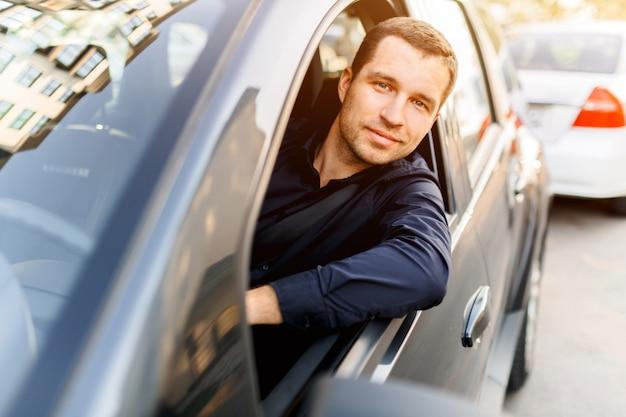 Jonge man in de donkere zwaardvechter rijden sobsvenno auto gluren uit