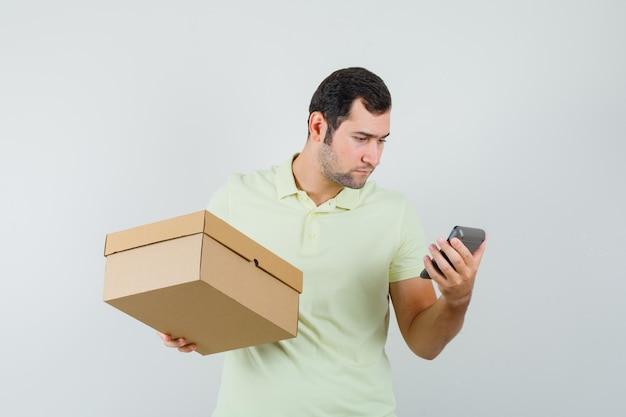 Jonge man in de kartonnen doos van de t-shirtholding, die rekenmachine, vooraanzicht bekijkt.