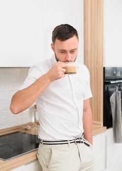 Jonge man in de keuken die een cappuccino nipt