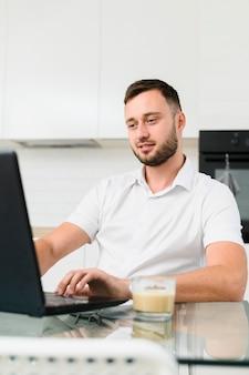 Jonge man in de keuken die op laptop werkt