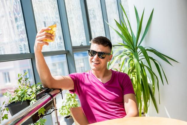 Jonge man in de kroeg. bier drinken, pizza eten.