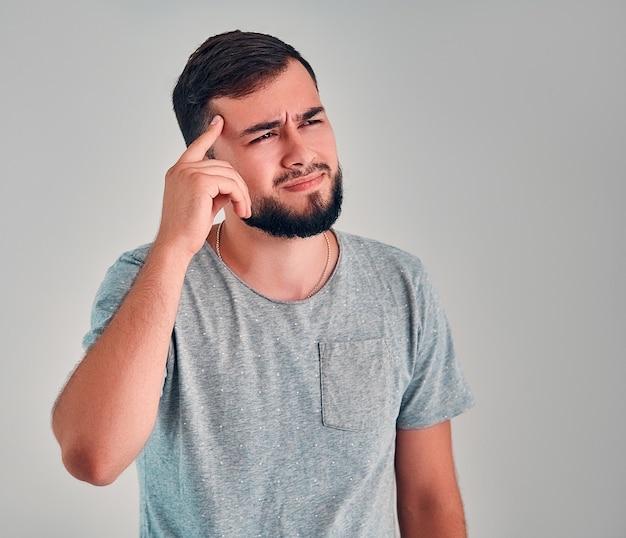 Jonge man in de studio op een grijze achtergrond
